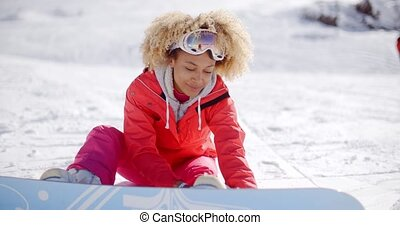 Skier attaching a snowboard to her boots - Smiling beautiful...