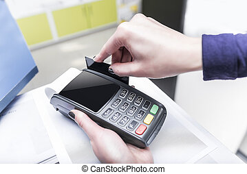 Debit card swiping on pos terminal - Payment card in a bank...
