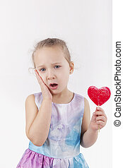 Toothache. Little girl with lollypop. - Toothache. Little...
