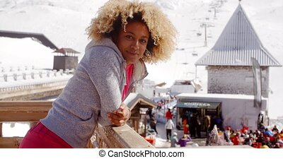 Smiling woman leaning on railing at ski resort - Side view...