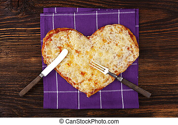 I love pizza. - Delicious pizza in heart shape on wooden...