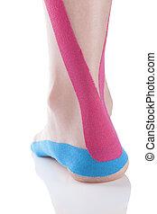 Kinesio tape on female heel. - Kinesio tape on female heel...