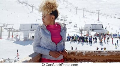 Trendy young woman at an alpine ski resort standing on the...
