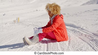 Woman in orange snowsuit sitting on ski slope - Single young...