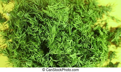 Chopped dill on a plate on the table rotates. Close-up