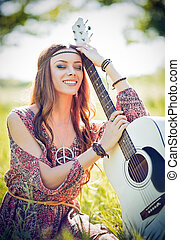 Portrait of beautiful smiling hippie woman with guitar....