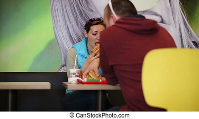 A man and woman eat burgers