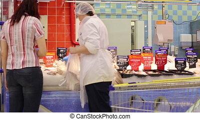 A woman chooses a fish shop - Caucasian woman chooses a fish...