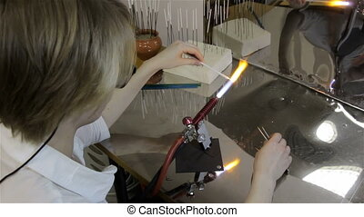 Woman producing glass bead in workshop