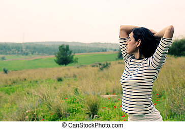 Woman with open arms standing outdoors