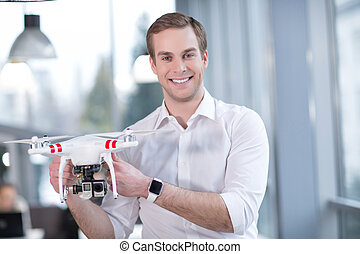 Attractive male freelancer is presenting a quadrocopter -...