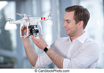 Skillful drone maker is working with joy - Waist up portrait...