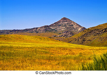 pyramidal mountain in field - pyramidal mountain in yellow...