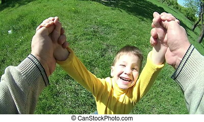 Father spinning his smiling son on green lawn in the sunny...