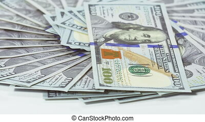 Many 100 US dollars bank notes rotating business background,...