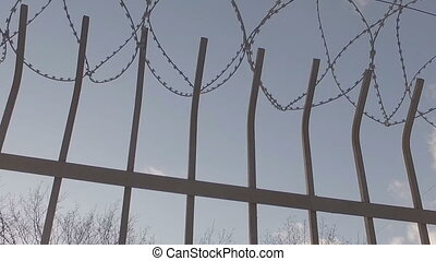 The iron fence and barbed wire against the sky