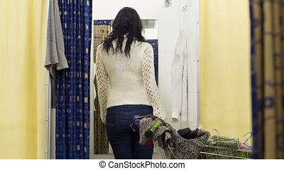 A woman in the booth takes clothes and pullovers