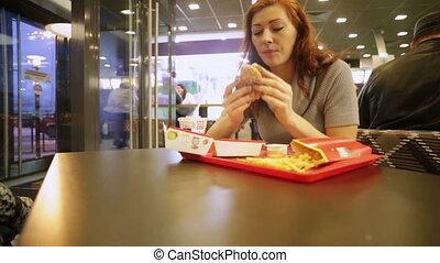 Woman eating hamburger and cola