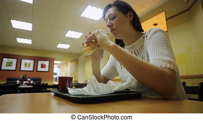 Woman eating a hamburger and drinking coffee