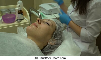 Ultrasonic face cleaning - Cosmetologist in beauty studio...