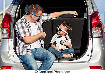 Happy father and son getting ready for road trip on a sunny...
