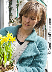 Buying Daffodils - Woman looking at a basket with daffodils...