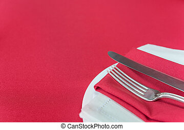 Elegant place settings on a red tablecloth - Silver knife...