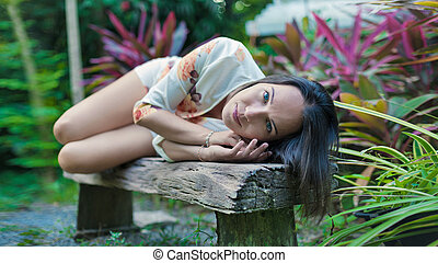 Beautiful woman is laying on the old wooden bench
