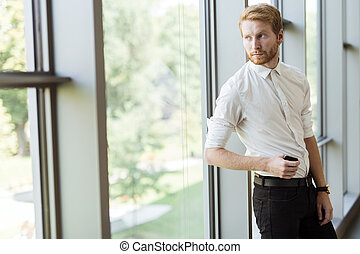 Successful businessman standing by the window - Portrait of...