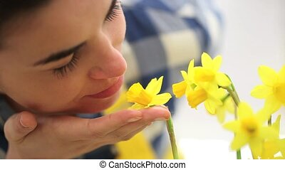 springtime, woman in garden touches and smells narcissus