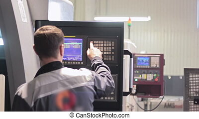 Operator working with control panel of CNC machining...
