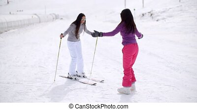 Young woman teaching her friend to ski at a winter mountain...