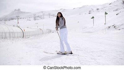 Cute woman on skis at bottom of hill - Single cute woman in...