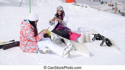 Young female friends relaxing with snowboards - Two...