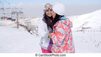 Two happy playful young ladies at a ski resort standing...