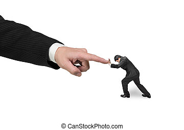 Small man pushing against big other hand forefinger,...