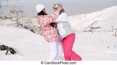 Young woman adjusting her friends ski goggles as they...