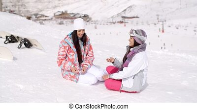 Two young female friends chatting in the snow - Two...