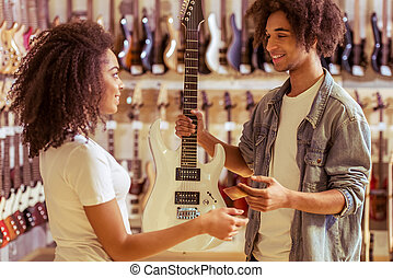 People in musical shop - Young Afro-American man holding an...