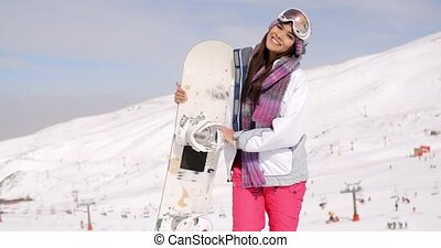 Smiling gorgeous woman posing with her snowboard - Smiling...