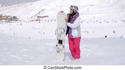 Young woman standing waiting with her snowboard - Young...