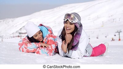 Laughing skiers laying on the ground - Cute pair of female...