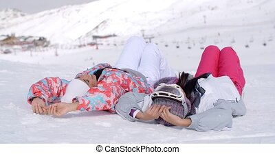 Two skiers laying on the ground - Two women in skiing...