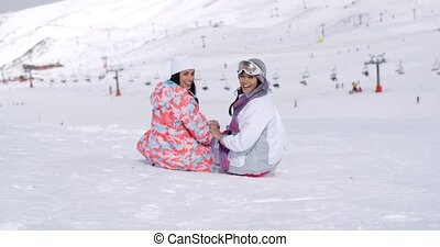 Two young women sitting in snow at a ski resort overlooking...