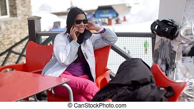 Young woman relaxing at an alpine ski resort sitting at a...