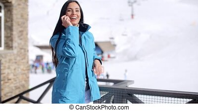 Attractive young woman at a mountain ski resort standing on...