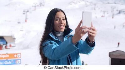 Smiling young woman taking a winter selfie as she poses on a...