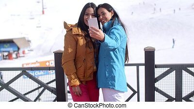 Two young women laughing at their selfie that they have just...