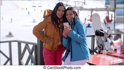 Two young woman checking out a selfie of themselves at a...