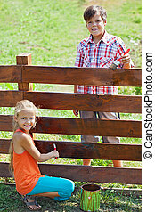 Young boy and girl painting a wooden fence